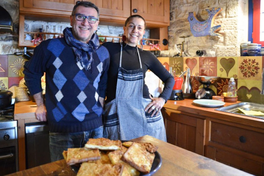"Lila and Pavlos with Lila's signature pie, ""kasiopita"" or ""alevropita"", a simple yet delicious comfort food."